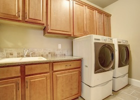 Laundry room with wooden storage cabinets and modern appliances